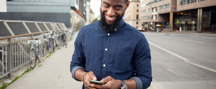 Man smiling and looking at phone